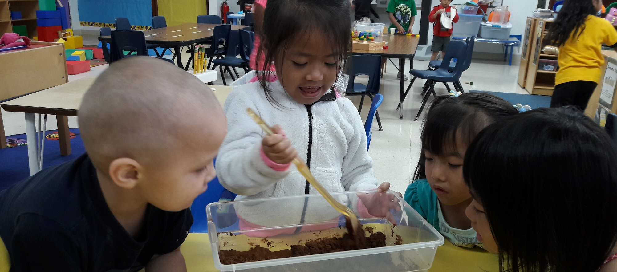 Kids in a classroom, mixing something in a container.